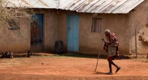 Senior woman walking through village in Tanzania